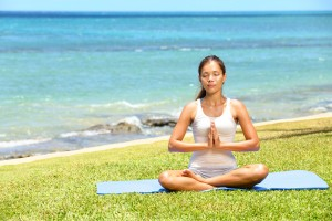 Yoga woman meditating woman relaxing by ocean sea doing the Sukh